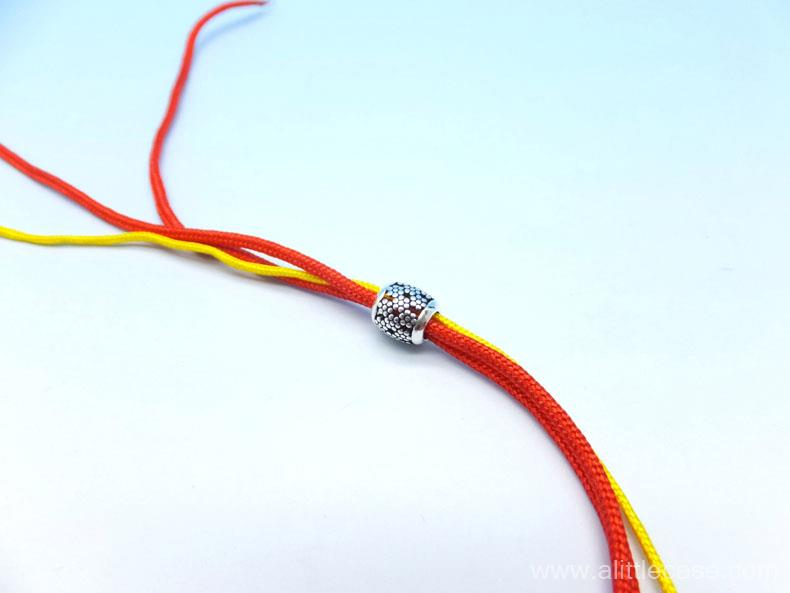 Picture of Thread a Bead and Move It to the Middle of Cords.