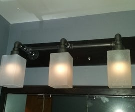 Black Pipe Vanity Light mounted on Wood Board