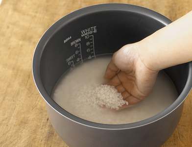 Put 2 Cups of Rice in a Rice Cooker Pot and Wash the Rice in Water.