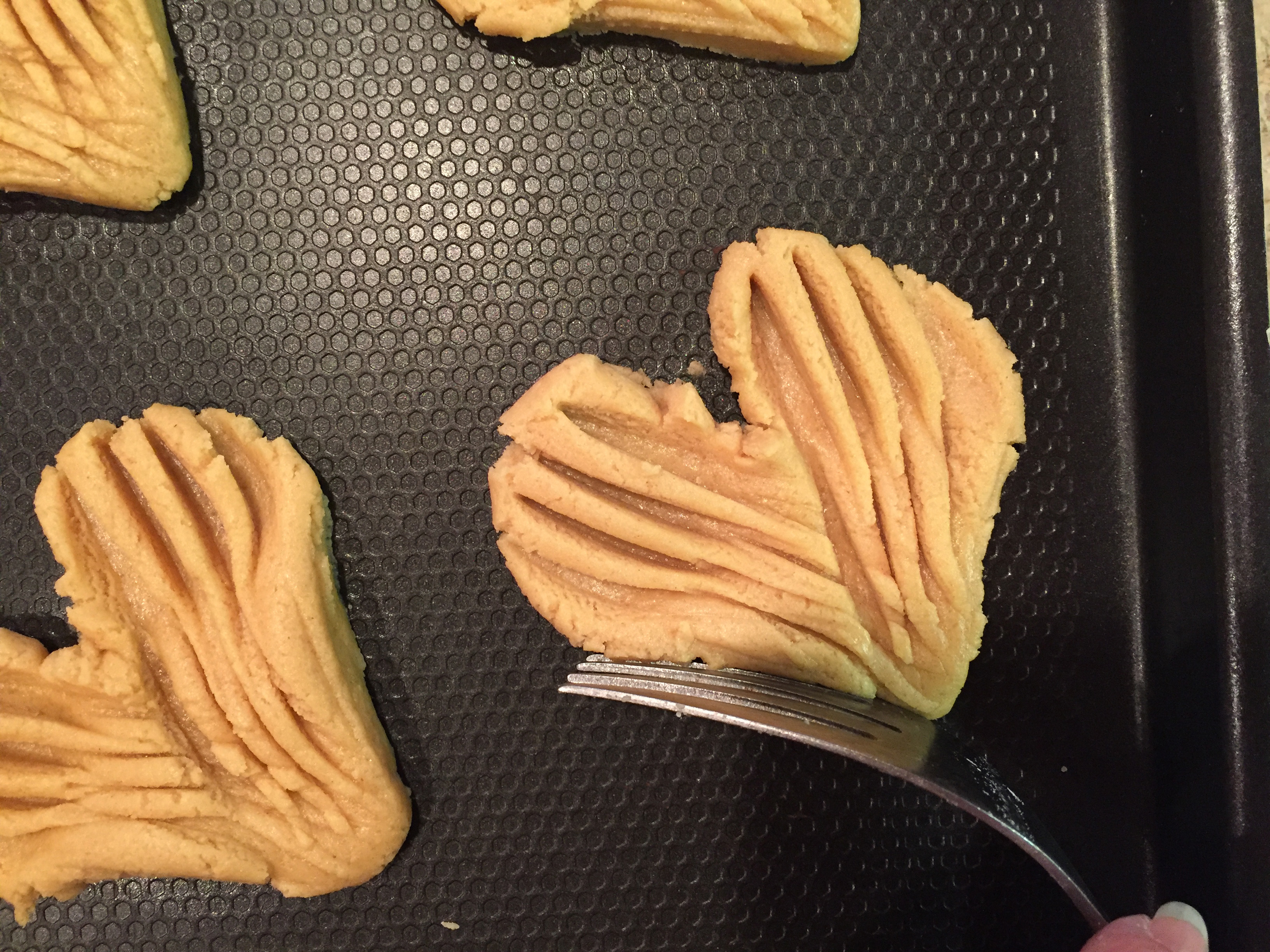 """Picture of Using Fork Edge Press the Bottom of the Cookie Inward (both Sides) to Make the Bottom """"V"""" Shape"""