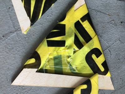 Sewing Strips of Caution Tape Around the Wooden Triangles.