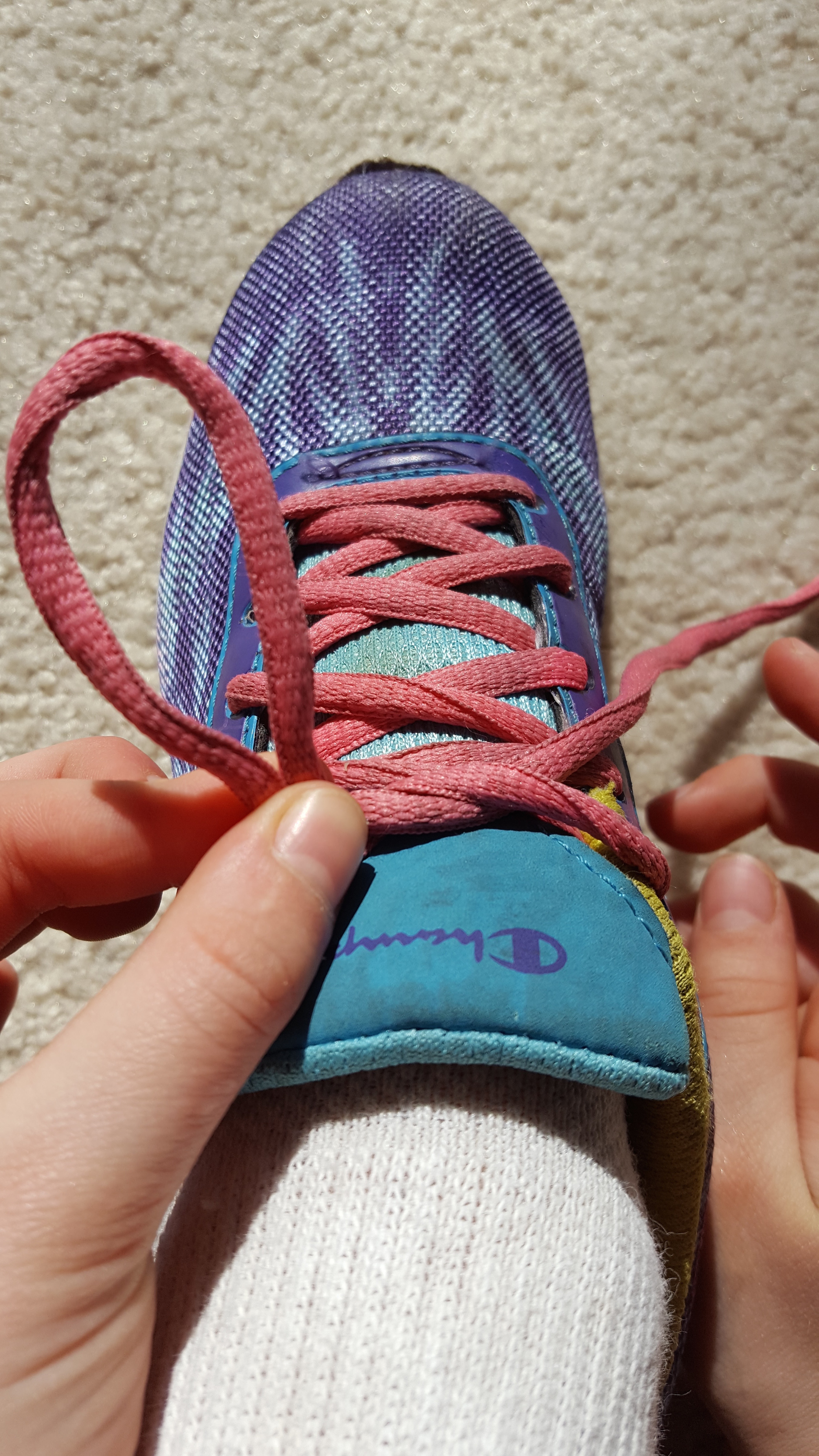 Picture of Make a Loop (Bunny Ear) on One Side of the Shoe. Hold the The Lace Higher Up With One Hand and Pinch It Together at the Bottom With the Other Hand.