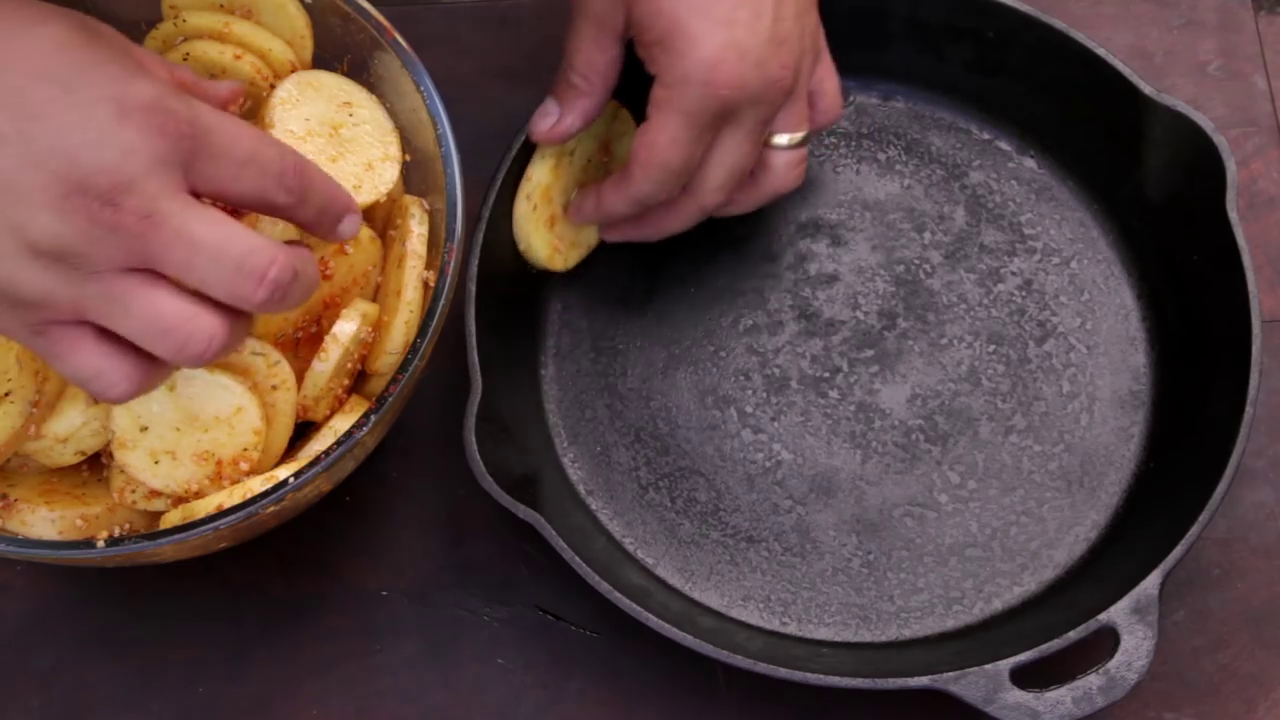Picture of In a Cast Iron Pan, Places the First Potato