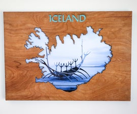 Wood Cutout of Iceland With Picture Behind It