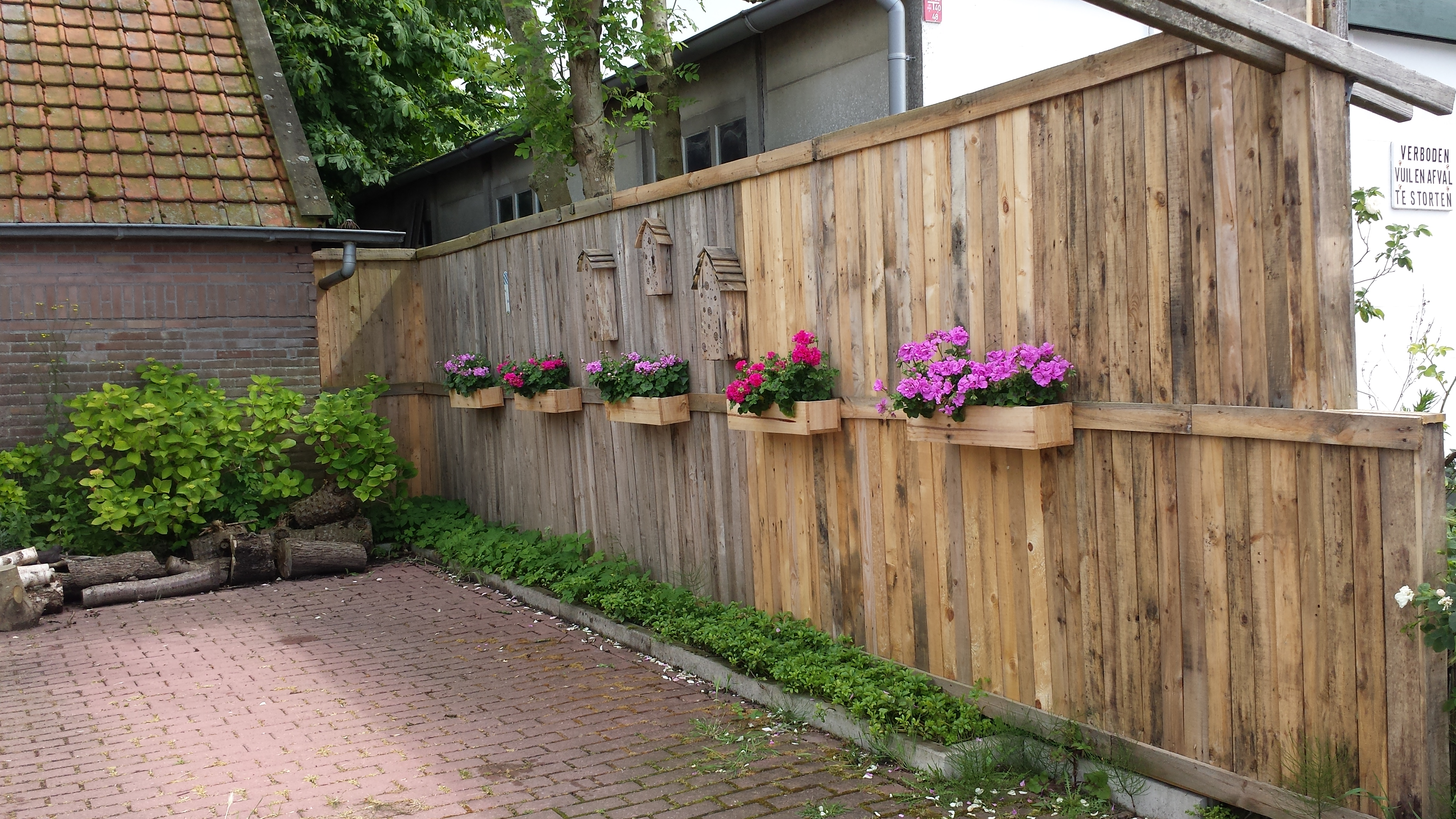 Picture of A Pallet Fence With Flower Boxes and Bee Hotels