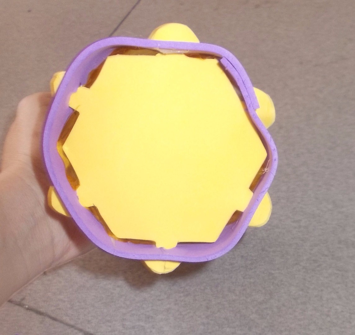 Picture of Poke the Arrow Tabs on the Foam Hexagon Onto the 6 Holes on the Bottom of the Lantern.