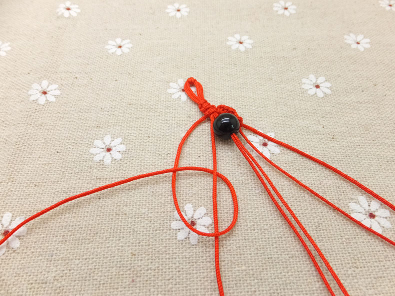 Picture of Now Pick Up the Outermost Cord on the Left Side and Make a Forward Knot by Creating a 4-shape Over the 2nd Cord.