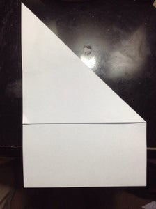 Then Fold the Top Right Corner to the Side of the Paper Forming a Triangle