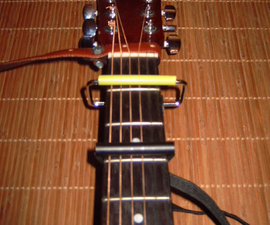 A guitar strap and 2 capos for the poor man