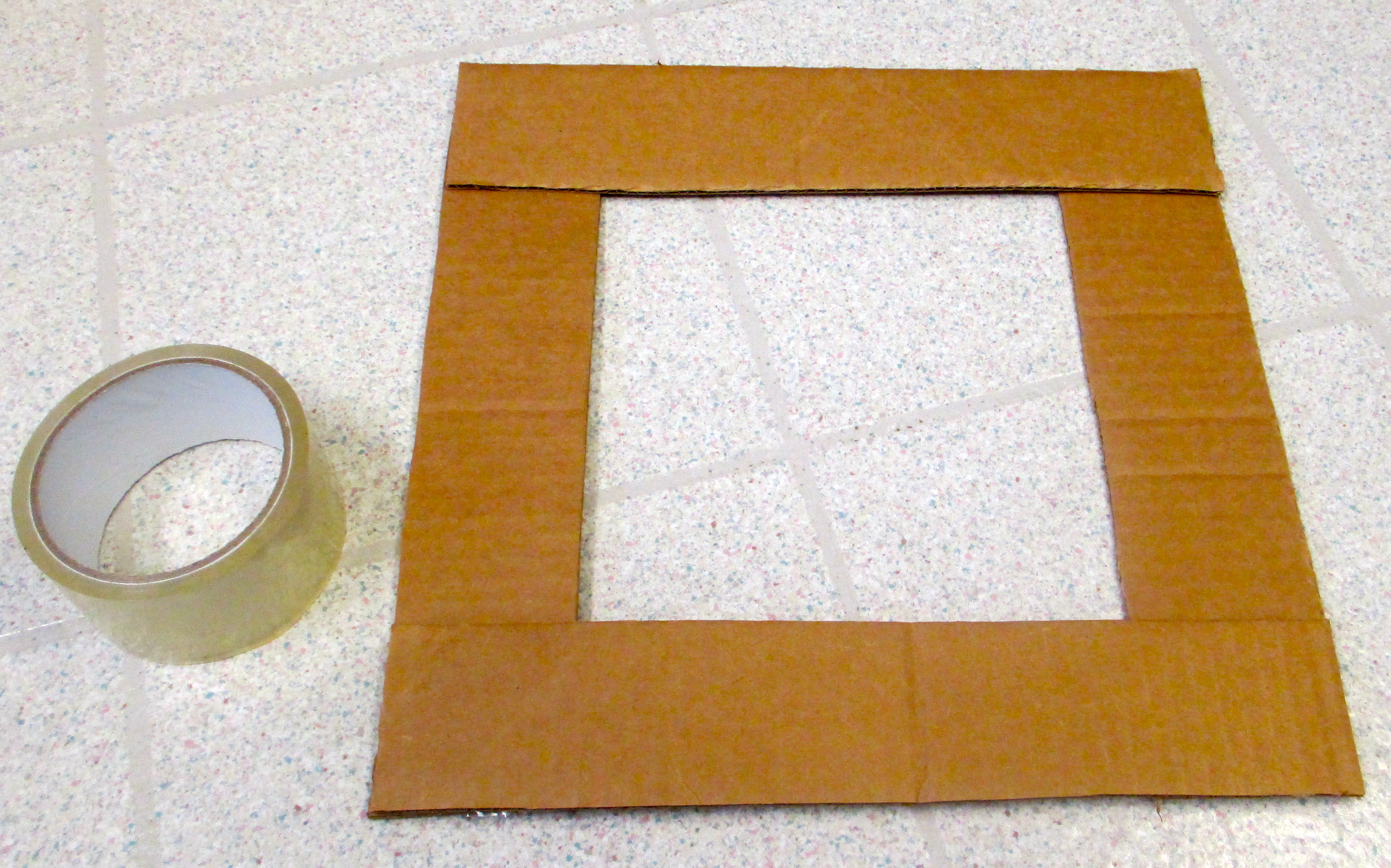 Picture of Use Double-sided Tape to Stick Together Corners of the 4 Strips.