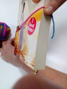 Start Your Tassle by Holding Yarn on Edge of Book