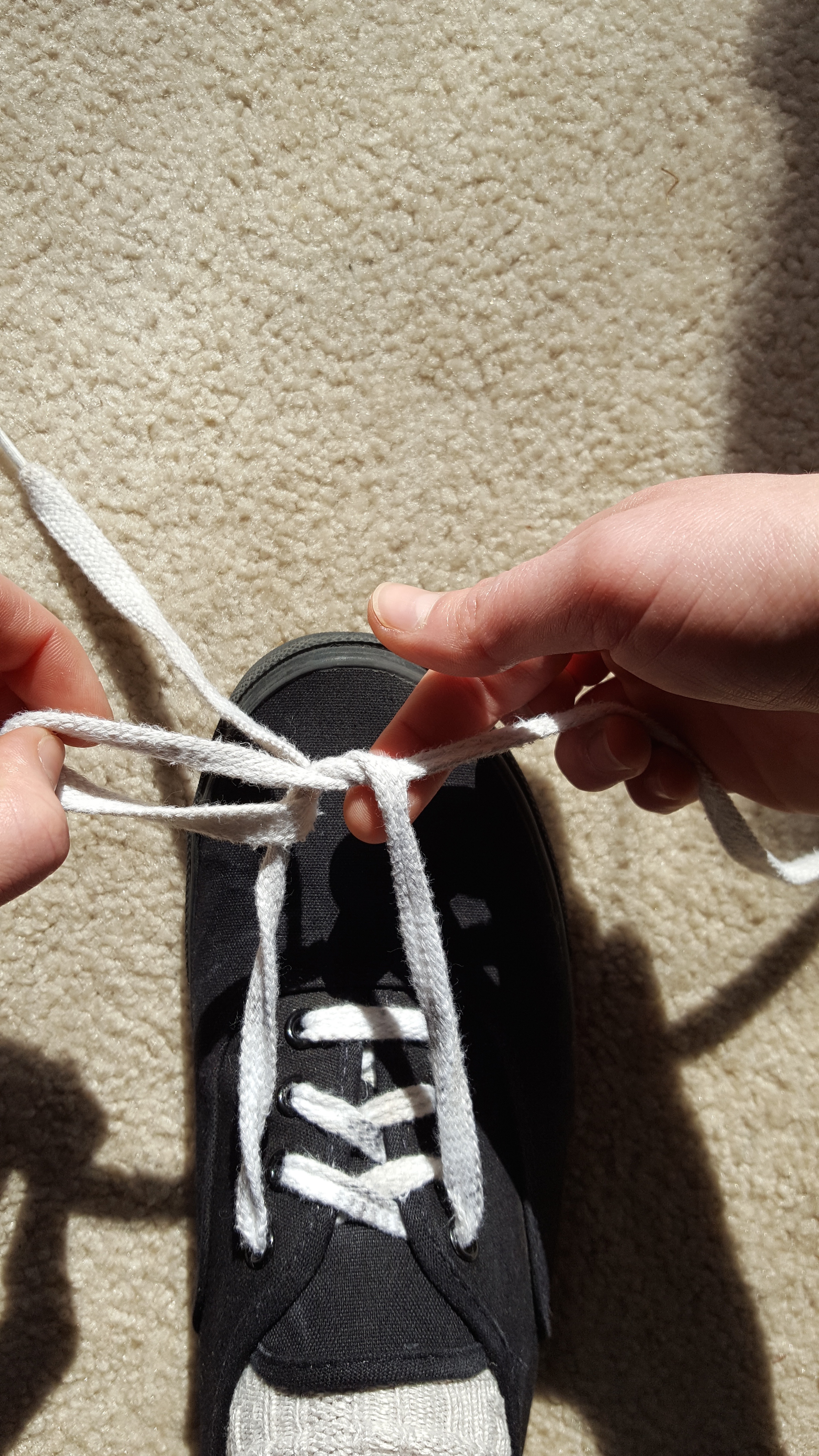 Picture of Continue Pulling the Right Lace All the Way Through (no Loops Yet!) While Holding on to the Left Lace.