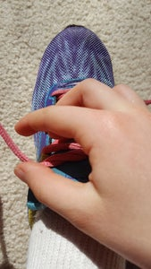Make a Loop (Bunny Ear) on One Side of the Shoe. Hold the The Lace Higher Up With One Hand and Pinch It Together at the Bottom With the Other Hand.