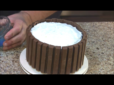 Picture of Cover the Sides of the Cake With Kit Kats.